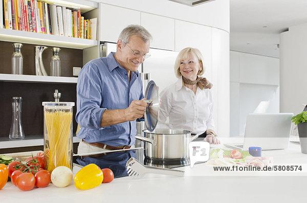 Seniorenpaar bereitet gesundes Nudelgericht in der Küche zu
