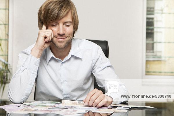 Lächelnder Mann am Schreibtisch schaut auf Geldscheine