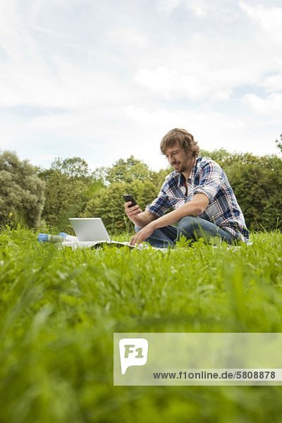 Young man using laptop and cell phone in meadow