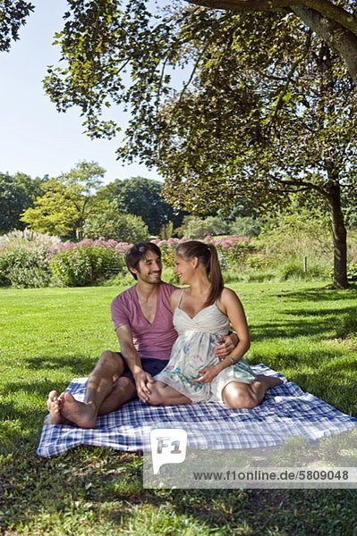 Man and pregnant woman on a blanket in a park