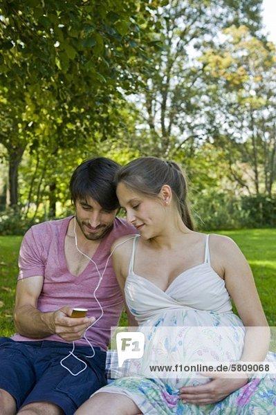 Mann und schwangere Frau hören Musik im Park