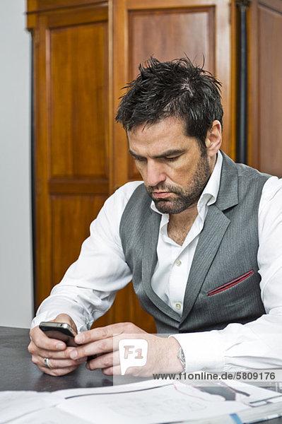 Mann am Tisch schaut auf sein Handy