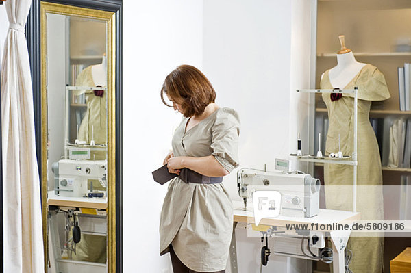 Frau probiert einen Gürtel im Schneideratelier an