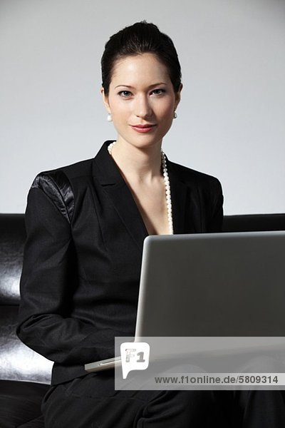 Businesswoman using laptop on couch