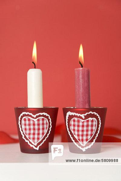 Zwei brennende Kerzen mit herzförmigem Kerzenhalter