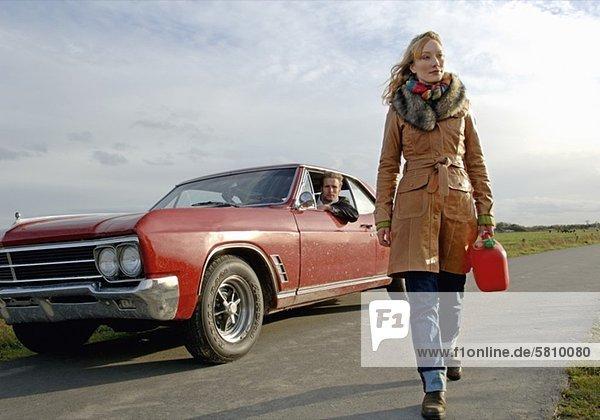 Frau geht mit Benzinkanister über eine Landstraße