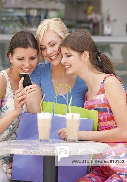 Drei fröhliche junge Frauen mit Handy und Einkaufstüten