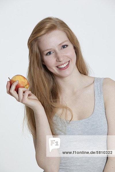 Rothaarige junge Frau hält einen Apfel