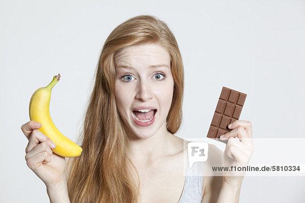 Rothaarige junge Frau hält eine Banane und Schokolade Rothaarige junge Frau hält eine Banane und Schokolade