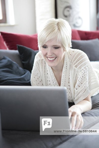 Smiling young woman using laptop on couch