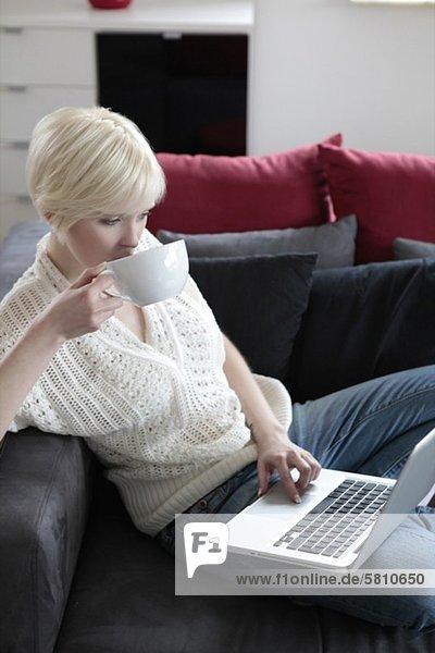 Junge Frau mit Laptop und Tasse auf der Couch