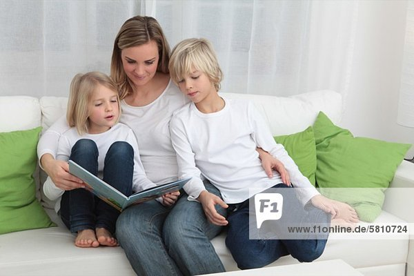 Mutter mit zwei Kindern liest ein Buch auf der Couch