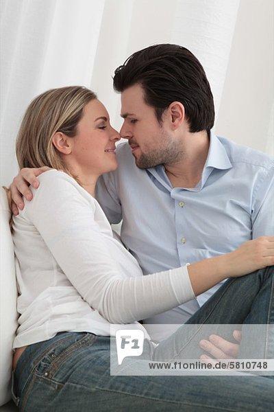 Zärtliches Paar sitzt auf der Couch
