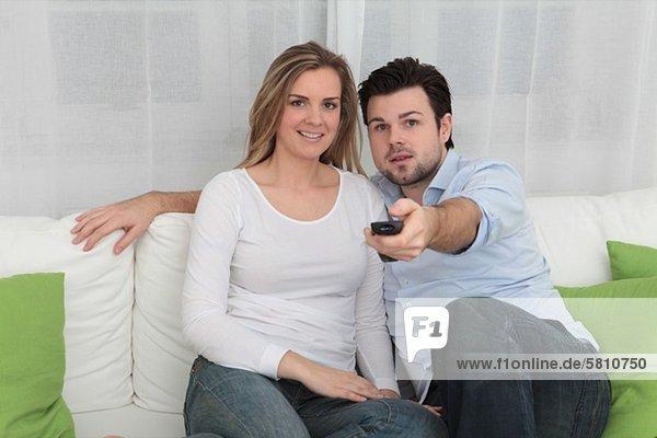 Paar auf einer Couch schaut fernsehen