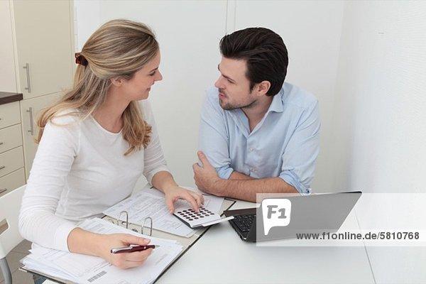 Mann und Frau sitzen am Tisch mit Akte  Taschenrechner und Laptop