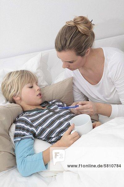 Mutter misst Fieber beim kranken Sohn im Bett