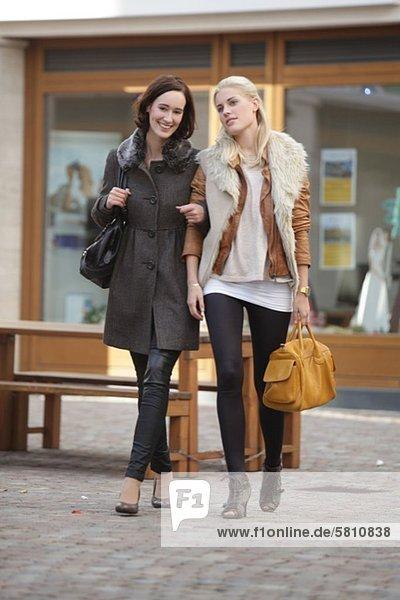 Zwei Freundinnen mit Handtaschen gehen Arm in Arm spazieren
