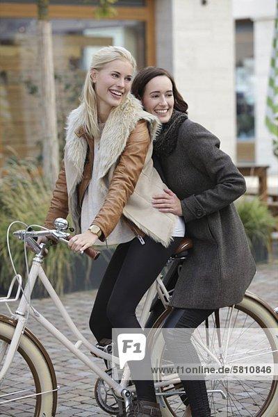 Zwei fröhliche Frauen zusammen auf einem Fahrrad