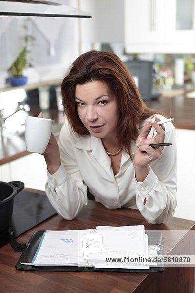 Frau in der Küche mit Kaffee  Zigarette und Terminkalender