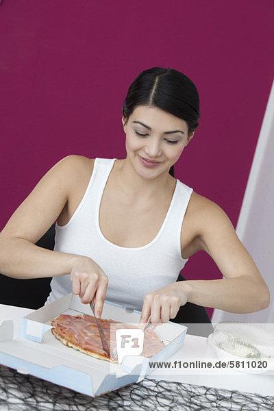 Junge Frau isst eine Pizza