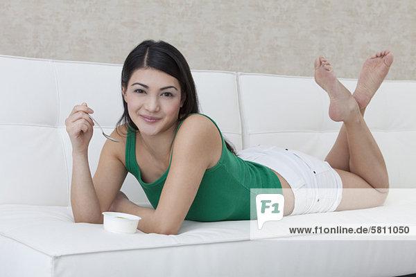 Dunkelhaarige junge Frau isst einen Joghurt