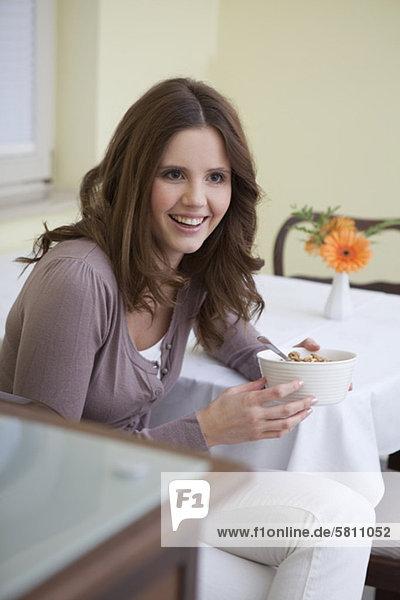 Glückliche junge Frau hält eine Schale mit Zerealien