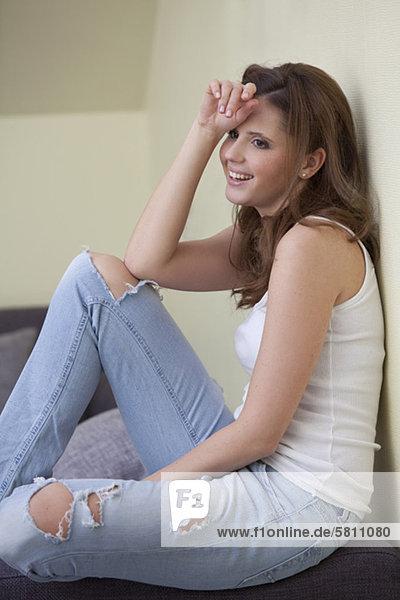 Fröhliche junge Frau sitzt im Wohnzimmer