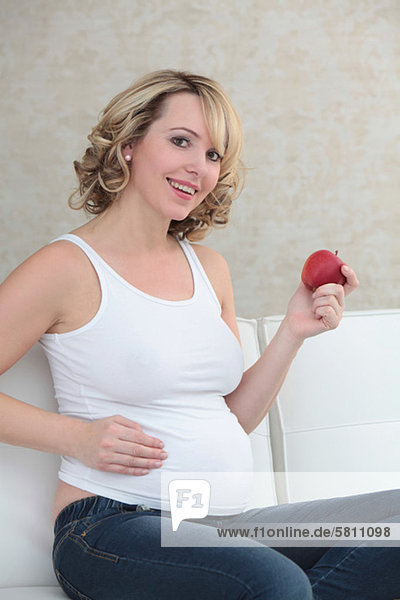 Schwangere Frau sitzt auf der Couch mit einem Apfel