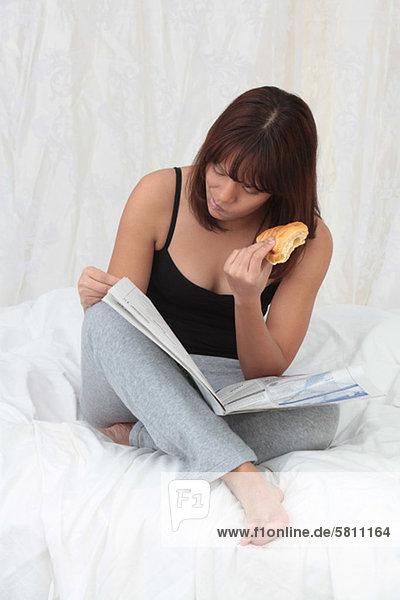 Frau Bett jung essen essend isst Croissant Zeitung vorlesen