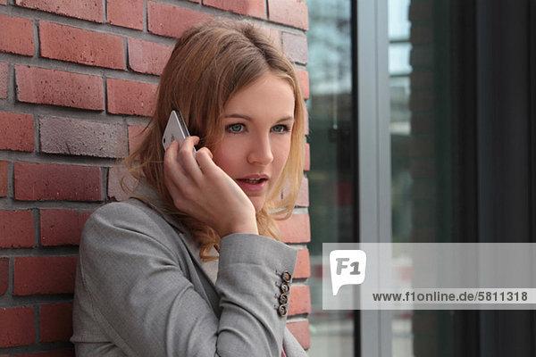 Handy blond Frau grau Sakko