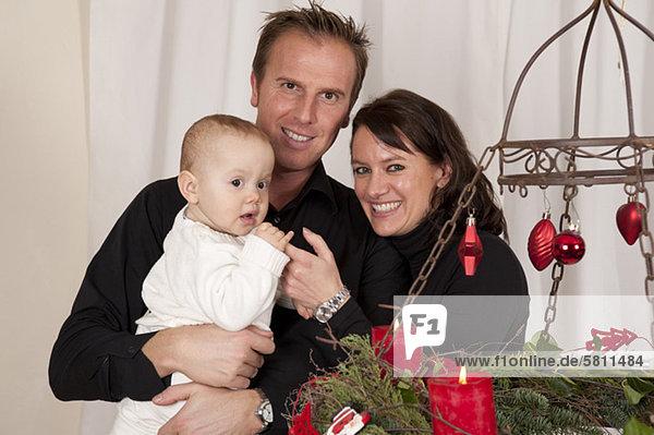 Glückliche Familie am Weihnachtskranz