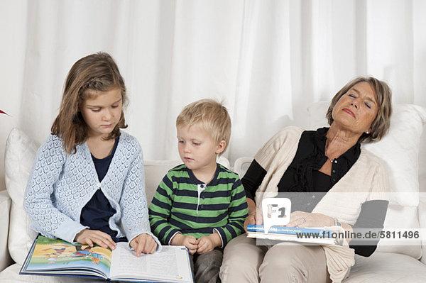 Junge und Mädchen mit erschöpfter Großmutter auf der Couch
