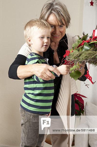 Großmutter und Enkelsohn schmücken den Weihnachtsbaum