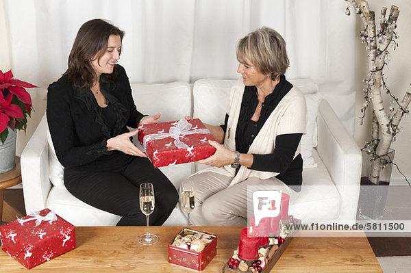 Mutter und erwachsene Tochter überreichen Weihnachtsgeschenke