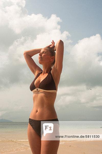 Frau in braunem Bikini steht am Strand  Thailand