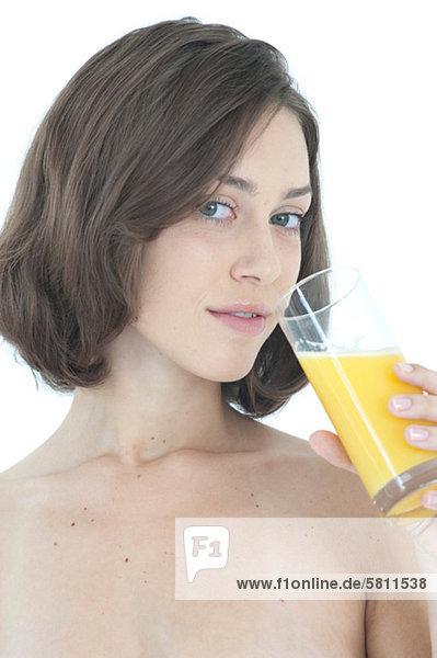 Brünette junge Frau trinkt ein Glas Orangensaft