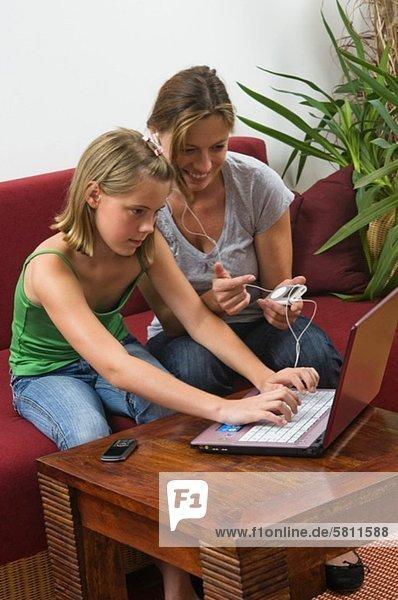 Tochter und Mutter mit Laptop und MP3-Player