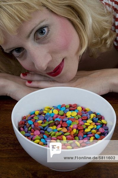 Junge Frau vor einer Schale mit Schokolinsen mund