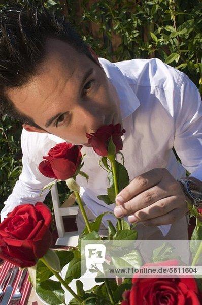 Junger Mann riecht an roter Rose
