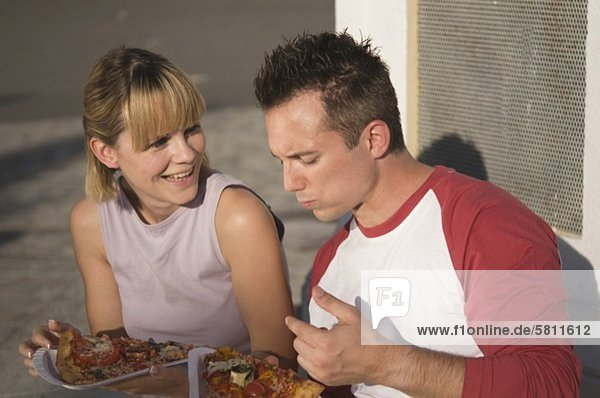 Young couple eating pizza outdoors