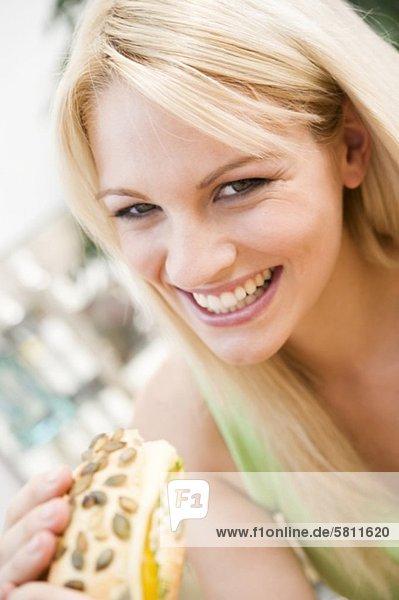 Fröhliche junge Frau hält ein Brötchen