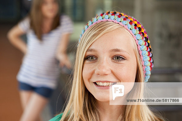 Smiling teenage girl in front of another teenage girl