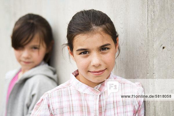 Lächelndes Mädchen lehnt an einer Betonwand