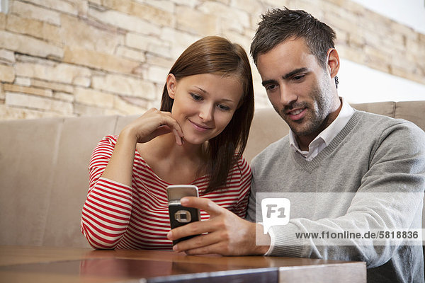 young couple looking at display of mobile phone