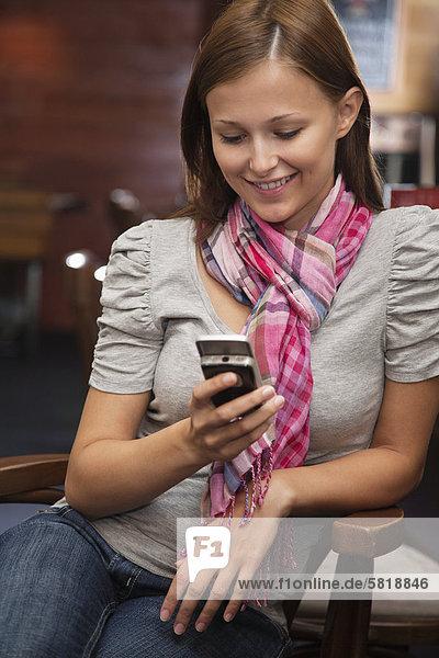 lächelnde junge Frau betrachten Display ihres Mobiltelefons
