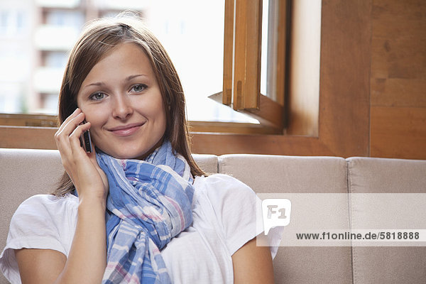 portrait of young woman sitting by window talking on mobile phone