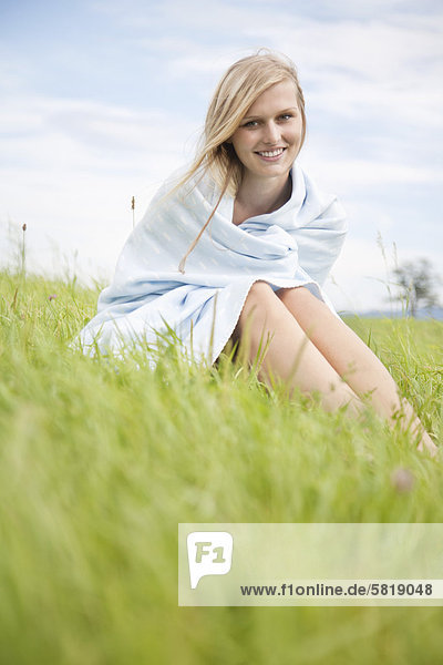 portrait of young woman covered with blanket sitting in grass