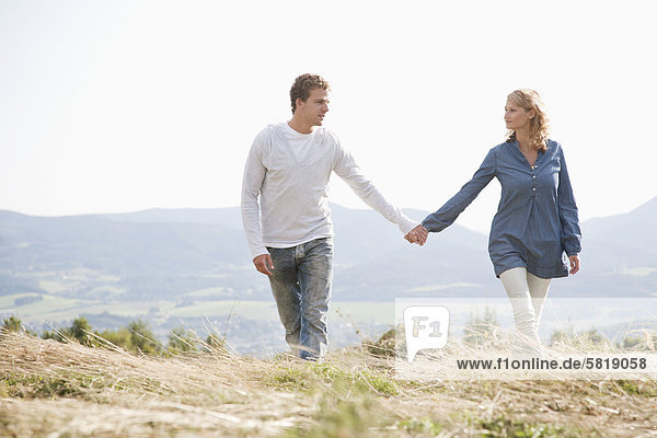 junges Paar Wandern durch Feld einher