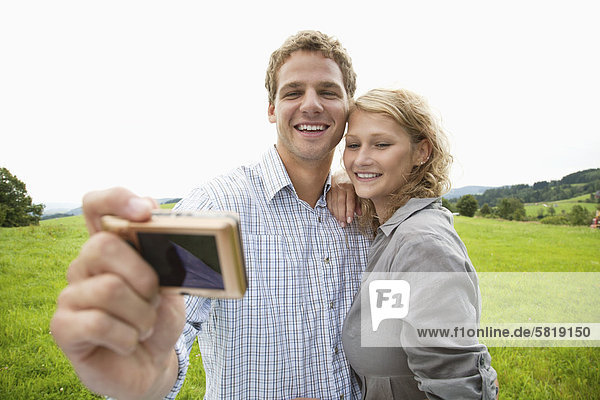 young couple taking self-portrait with digital camera