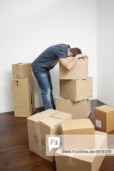young man searching for something in moving boxes